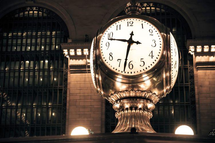 Illuminated clock tower at railroad station at night
