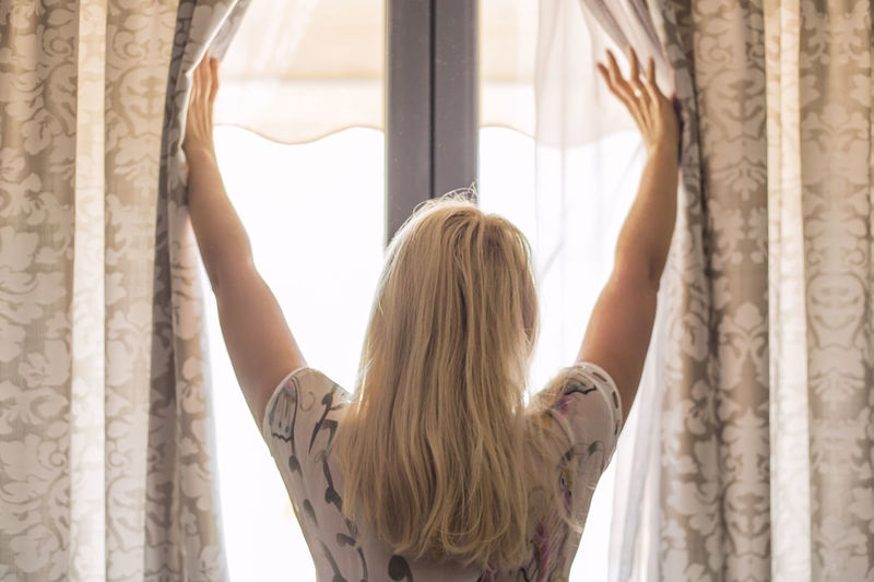 Blond Hair Curtain Day Drapes  Home Interior Indoors  Leisure Activity Lifestyles Long Hair One Person People Real People Rear View Standing Window Women Young Adult Young Women