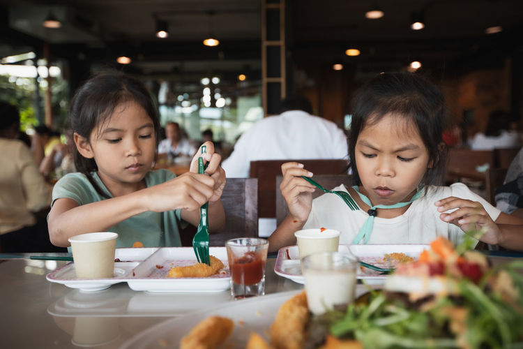 Cute sisters eating food while sitting at restaurant