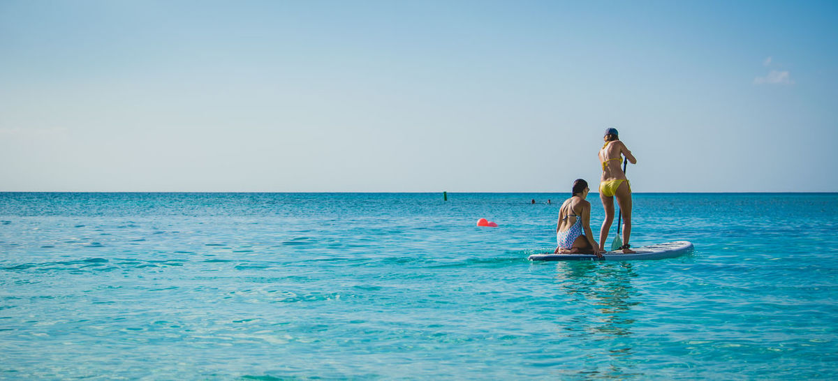 Two Girls on a Paddleboard SAP Beach Photography Caribbean Island Dream Destination Panorama Tropical Paradise Adventure Bikini Blue On Blue  Cayman Islands Clear Sky Healthy Lifestyle Horizon Over Water Nature Ocean Outdoors Paddleboarding Sexygirl Sports Summer Travel Destinations Two People Vacation Vacations Water Women
