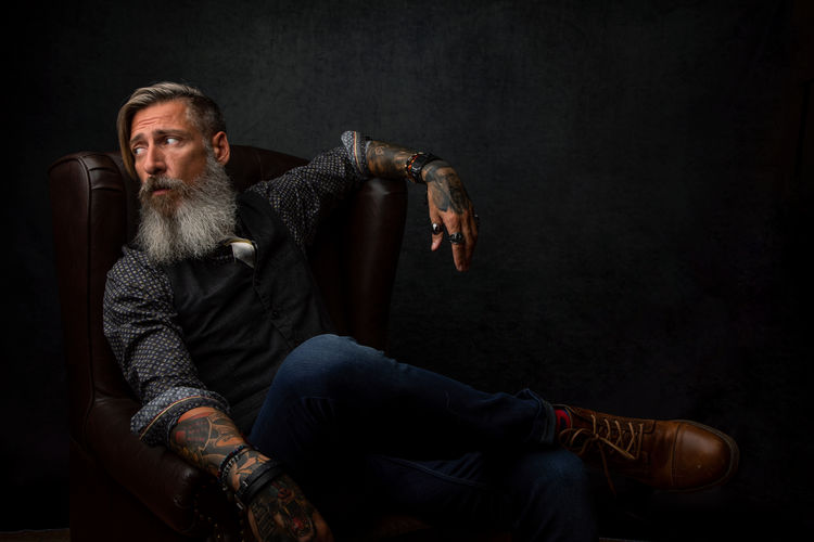 Hipster man sitting on armchair against gray wall