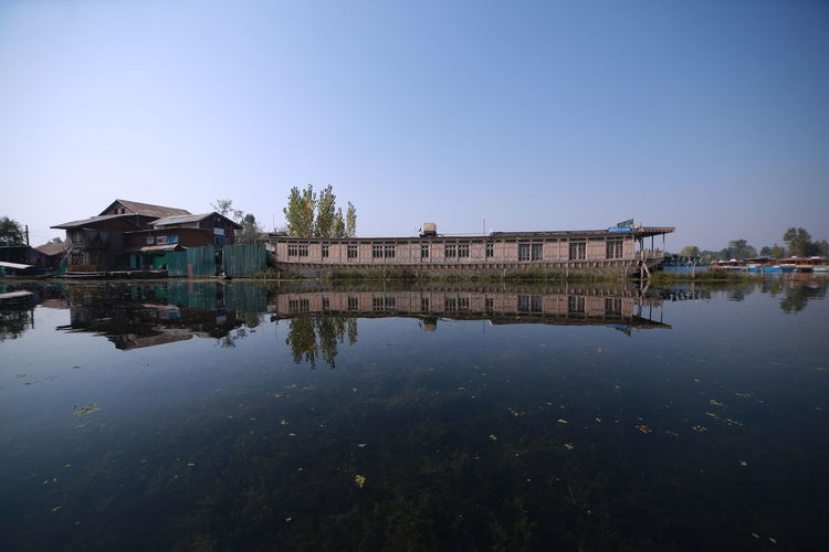 Reflection of building in lake against clear sky