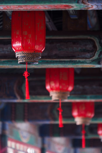 Close-up of red bell hanging in temple