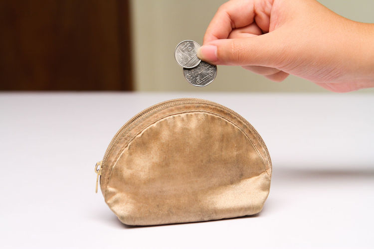 Cropped hand putting coins in purse on table