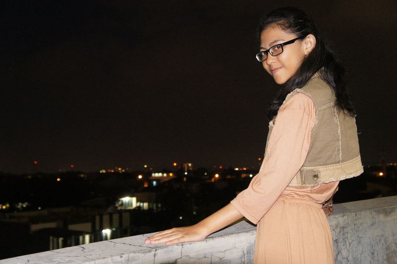 Portrait of young woman in sunglasses standing against clear sky at night