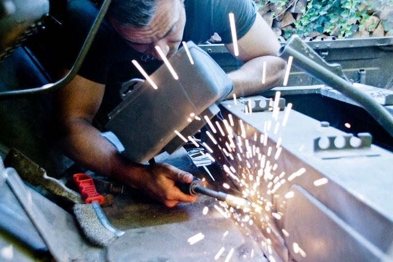 Young man welding metal in workshop