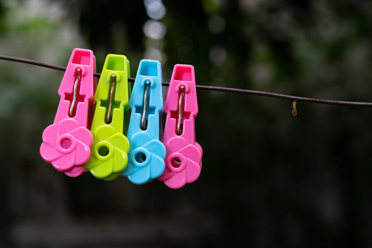 Close-up of multi colored clothespins hanging on rope