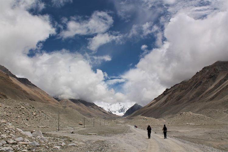 People walking on dirt road against sky