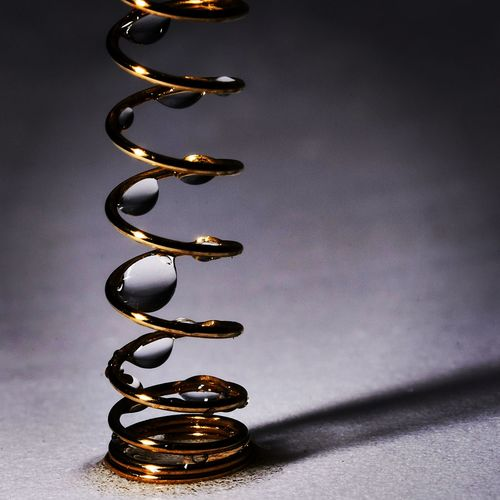 Close-up of spiral with water drops over table
