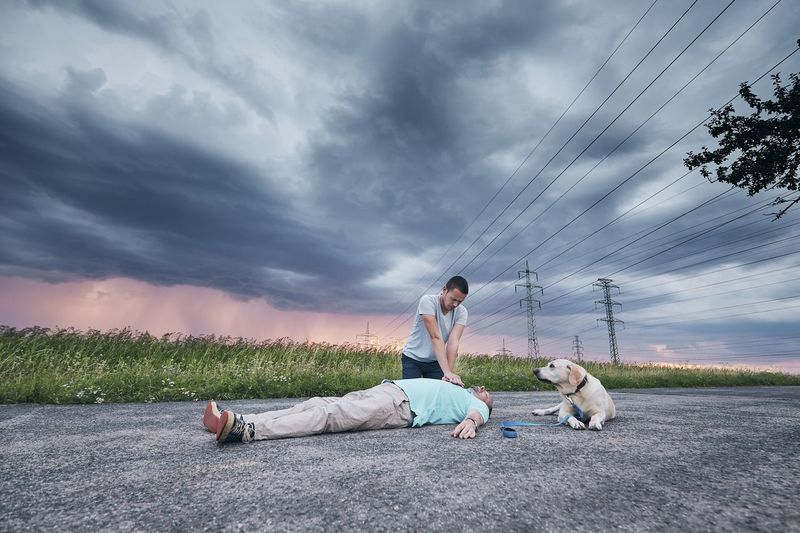 Man giving cpr to unconscious man by dog on road against cloudy sky