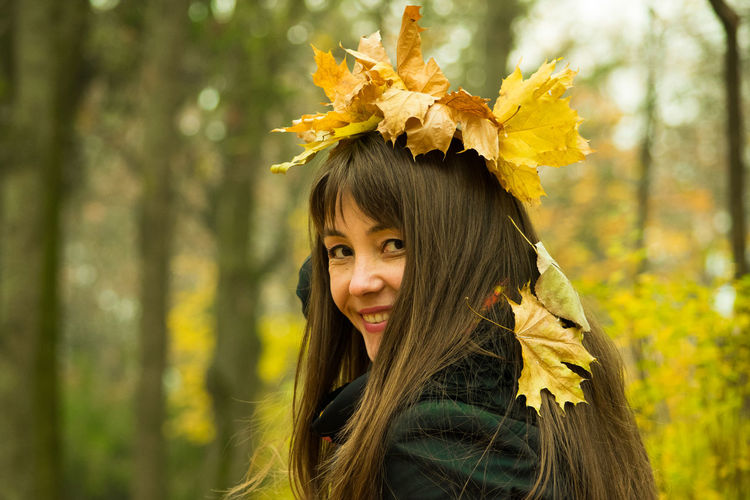 Portrait of smiling mid adult woman with autumn leaves on head at park