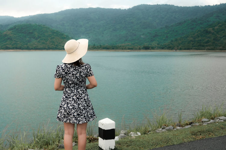 Real People Leisure Activity One Person Lifestyles Hat Women Water Clothing Plant Nature Outdoors Standing Lake Three Quarter Length Day Scenics - Nature Non-urban Scene Beauty In Nature Rear View Mountain Sun Hat