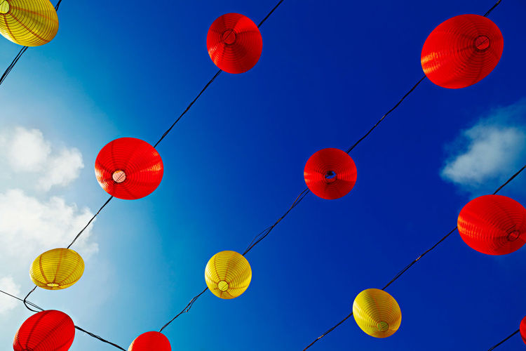 Low angle view of lanterns hanging against blue sky