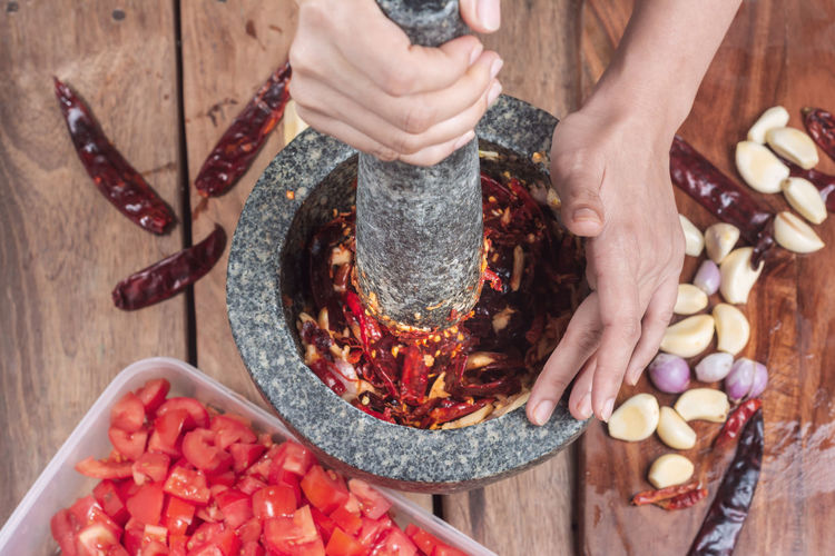Cropped hands of woman crushing red chili pepper in mortar and pestle