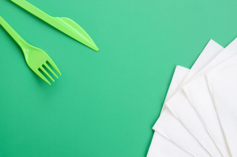 High angle view of plastic cutleries with tissue papers on green background