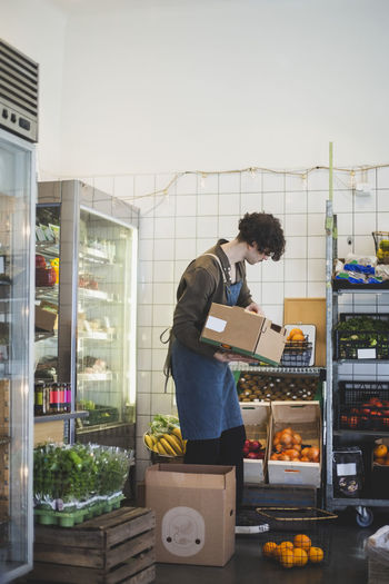 Side view of a man holding food at store