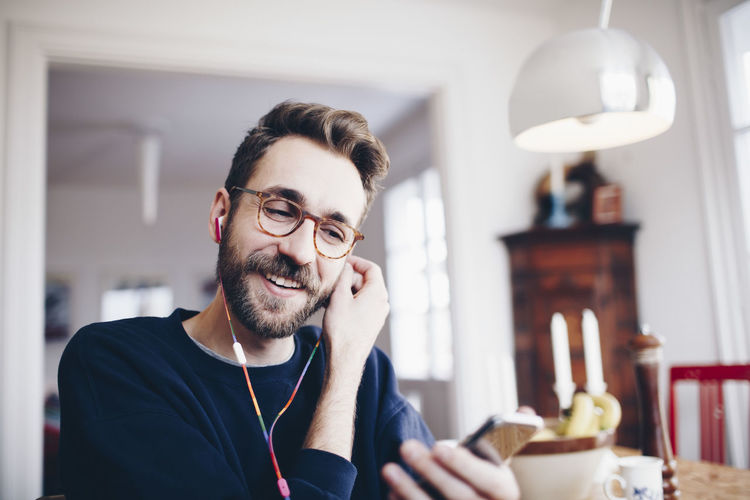 Happy man listening to music in mobile phone at home