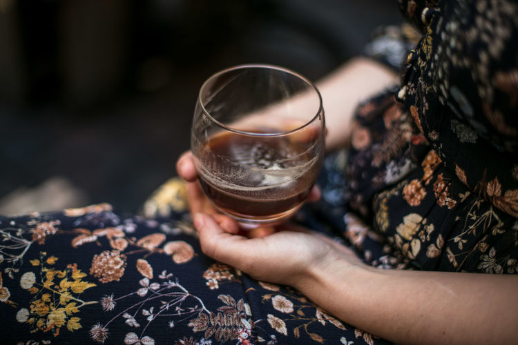 Midsection of woman holding alcohol glass
