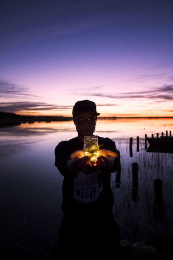 Man holding illuminated lights in glass jar while standing against sea and sky during sunset