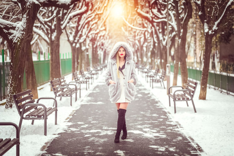 Portrait of woman in snow covered street in city