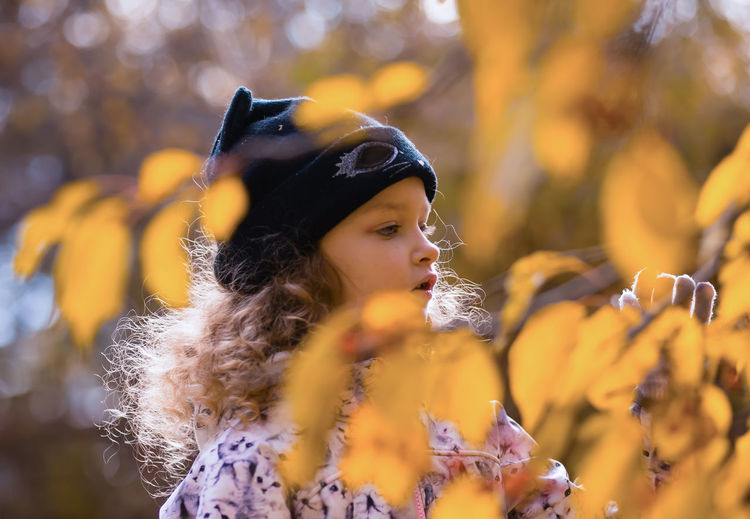 Close-up of young woman with autumn leaves