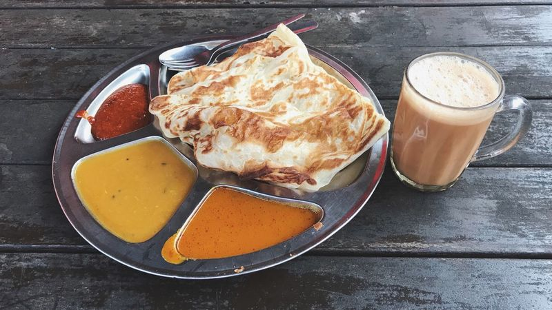 EyeEm Selects Roti canai with dhal curry and Teh Terik isolated on rusty wood background. Asian or Indian tradition food Food And Drink Food Freshness Ready-to-eat No People Table Healthy Eating Plate Indoors  Close-up Comfort Food Day Roti Canai Teh Tarik Wood - Material Wood Indian Cultures Travel Travel Destinations Curry Streetphotography Still Life Flatlay