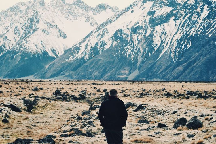 Rear view of man standing in front of mount cook