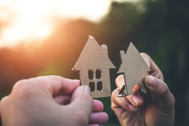 Cropped hands of people holding model house during sunset