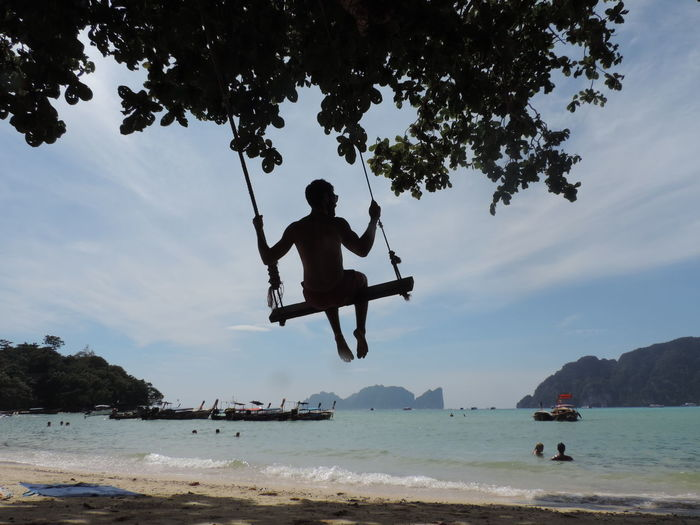 Swing in Thailand Tree Water Sky Sea Nature Real People Men Leisure Activity Lifestyles Beach Day Beauty In Nature Mid-air Outdoors Scenics - Nature Cloud - Sky Balance Swing Thailand Travel Travel Photography EyeEmNewHere