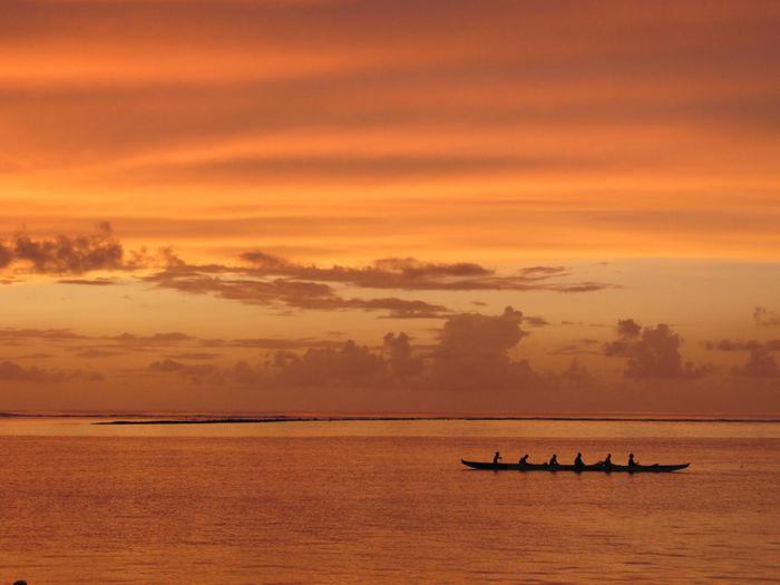 Six People Paddling On Canoe At Sunset