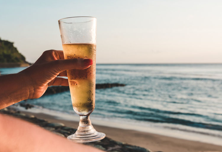 Hand holding glass of beer against sky at the beach