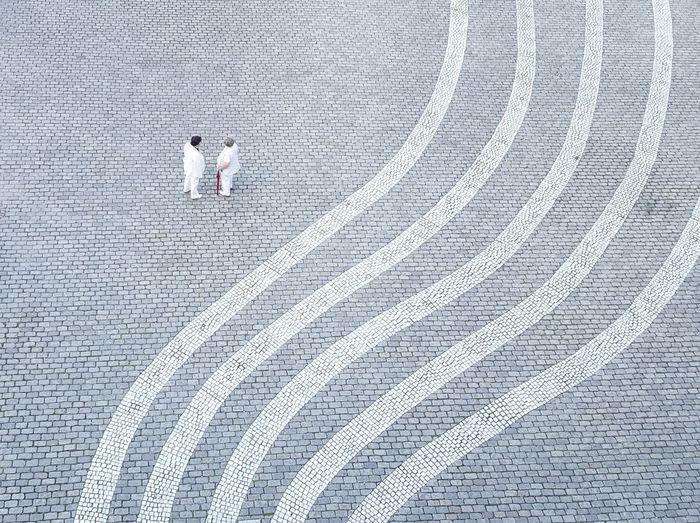 View of two elderly women talking on cobblestone square