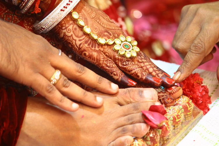 Close-Up Of Person Touching Bride And Groom Feet