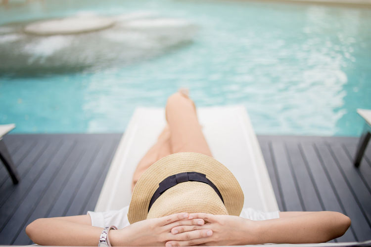 Woman Sitting On Lounge Chair At Poolside