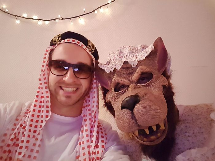 Portrait of happy friends in costume at home during party