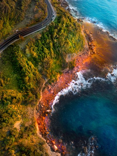 Aerial view of road by sea during sunset