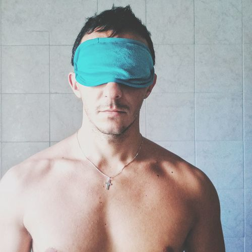 Shirtless young man wearing sleep mask while standing against tiled wall at home