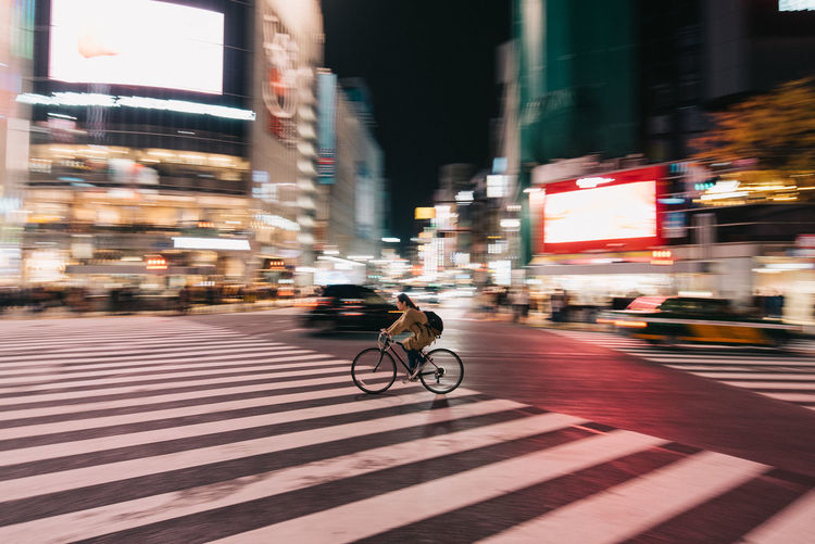 City Transportation Architecture Building Exterior Street Built Structure Bicycle Mode Of Transportation Motion City Life Blurred Motion Crosswalk Land Vehicle Zebra Crossing Road Ride Crossing Riding Night People Outdoors Alone