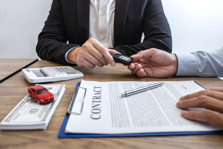Agent giving car key to customer by papers and currency on table