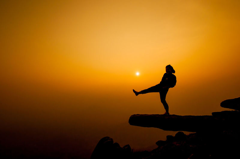 Silhouette Woman Kicking On Cliff Against Sky During Sunset