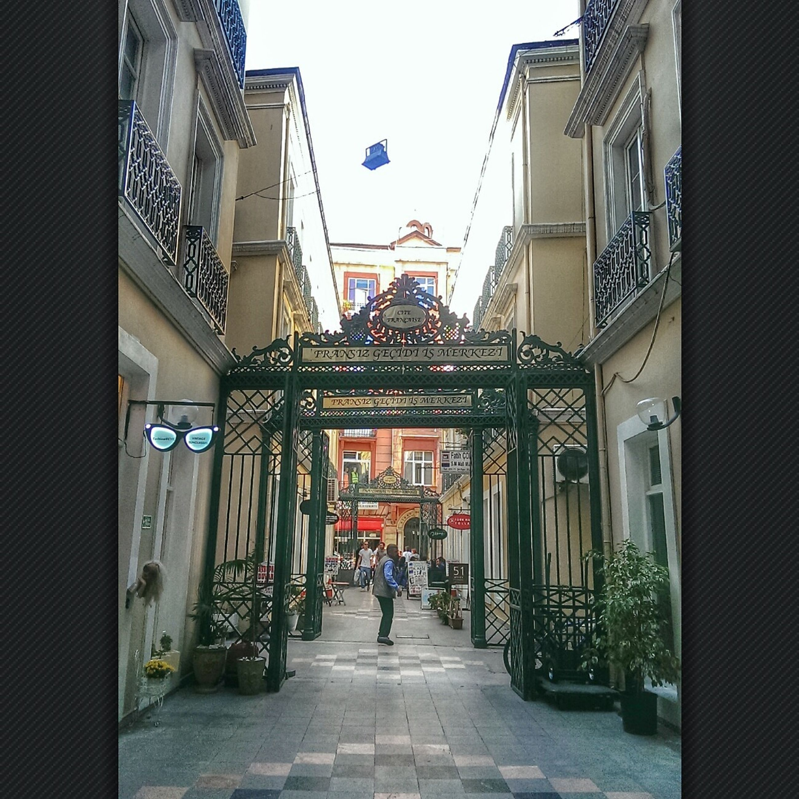 architecture, built structure, building exterior, the way forward, street, city, building, residential building, incidental people, diminishing perspective, day, clear sky, residential structure, outdoors, cobblestone, entrance, bicycle, city life, alley, house