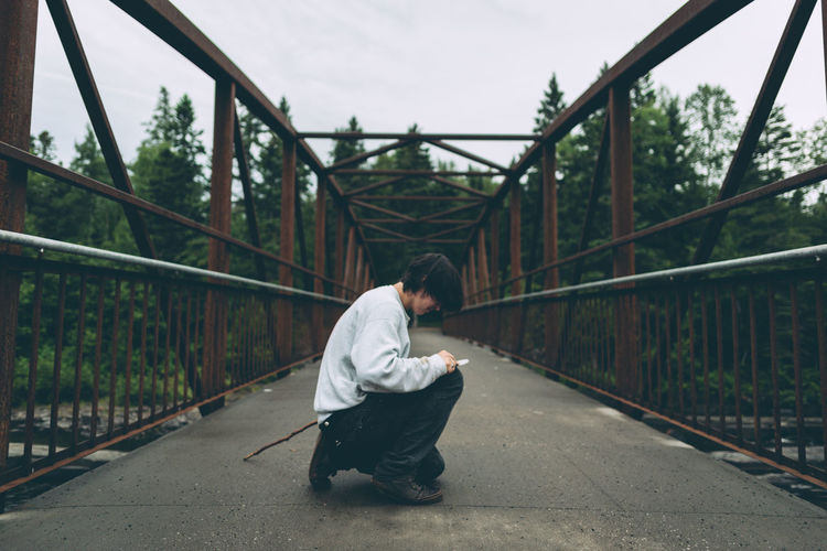 Crouching Bridge Casual Clothing Crouching Day Diminishing Perspective Direction Full Length Leisure Activity Lifestyles One Person Outdoors Real People Side View Sitting Teenager The Way Forward Young Adult