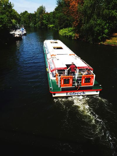 boat on the river Trave in Lübeck Sonnig Sunny Green Plant Life River Riverview Landscape Waterscape Bridgeview ARTfoxHH Lübeck Water Nautical Vessel Tree River High Angle View Motorboat Floating On Water Countryside