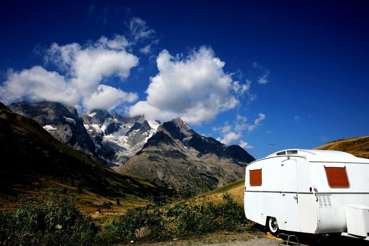 Motor Home By Rocky Mountains Against Sky