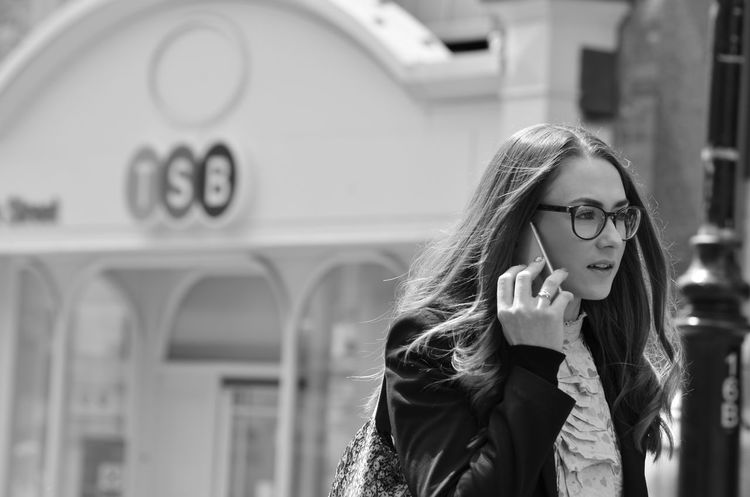 Communication Day Eyeglasses  Focus On Foreground Front View Leisure Activity Lifestyles Long Hair Mobile Phone One Person Real People Standing Wireless Technology Young Adult Young Women