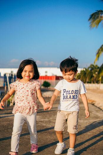 Full length of siblings holding hands walking on street