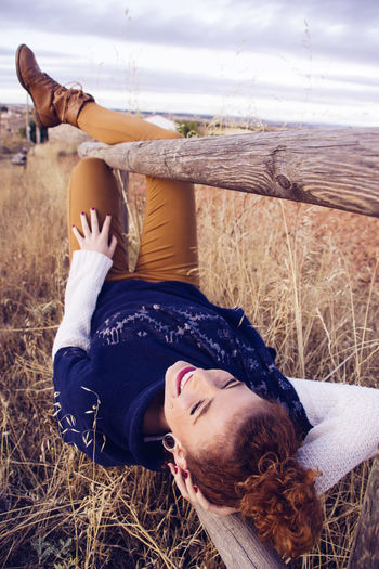 Happy young woman lying on railing at field