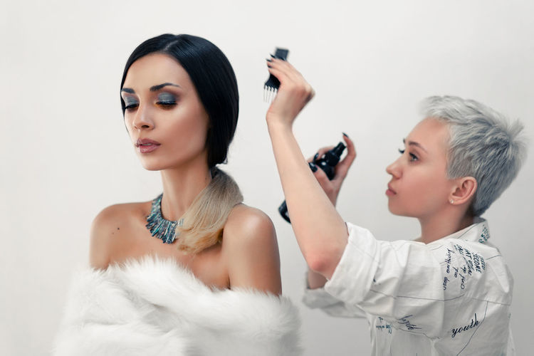Beautician applying make-up to fashion model against white background