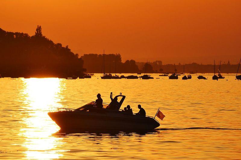 Silhouette people on motorboat in river against orange sky