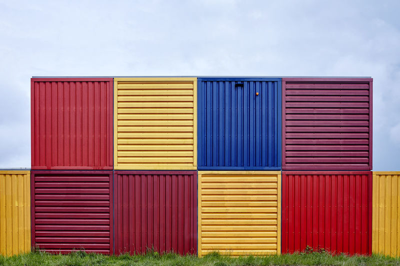 Multi colored cargo containers against sky